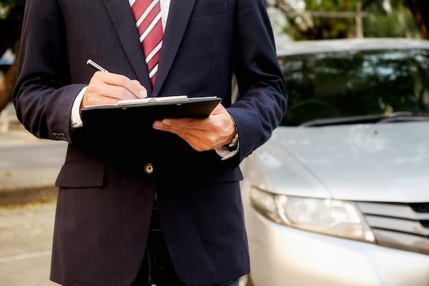 Il est temps de prendre une décision. jeune homme d'affaires confiant travaillant sur son lablet et parlant au téléphone assis dans la voiture