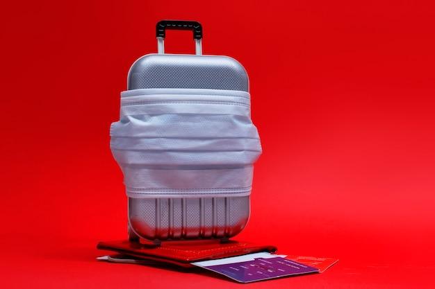 Il est temps de voyager. annulation de vol et concept de repos sûr pendant une pandémie de coronavirus covid-19. valise de voyage avec masque médical et billets d'avion avec passeport.