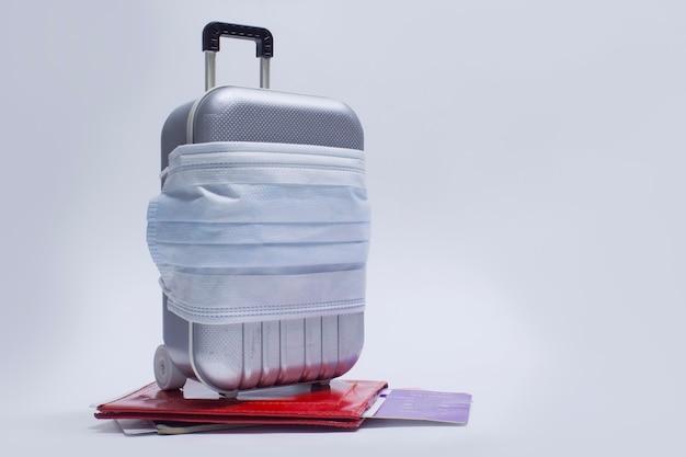 Il est temps de voyager. le concept de repos sûr pendant une pandémie de coronavirus covid-19. valise de voyage avec masque médical et billets d'avion avec passeport.