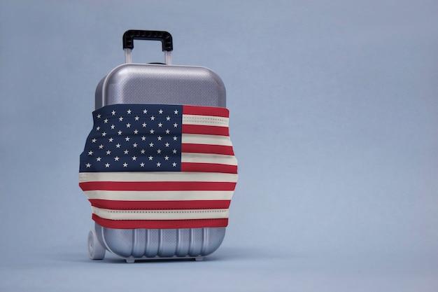 Il est temps de voyager. le concept de repos sûr pendant une pandémie de coronavirus covid-19. valise de voyage avec masque médical et drapeau usa.