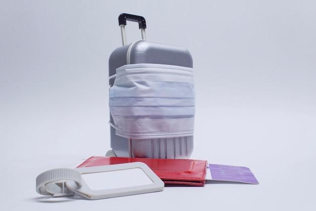 Il est temps de voyager. le concept de repos sûr pendant une pandémie de coronavirus covid-19. valise de voyage avec masque médical