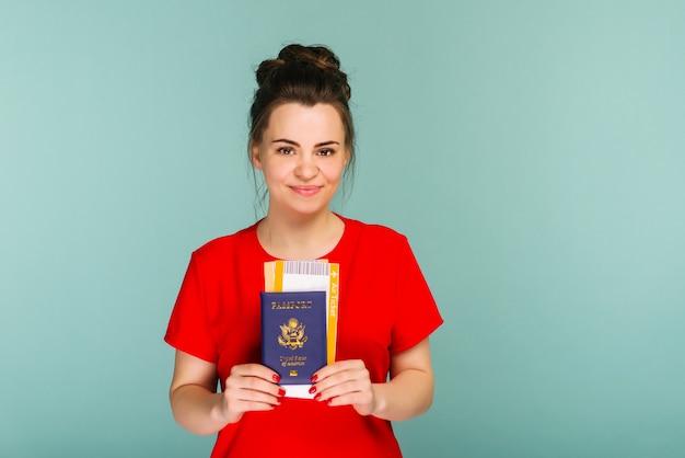 Il est temps de voyager. une femme souriante à la mode moderne en robe rouge avec des billets d'avion et un passeport à la main.