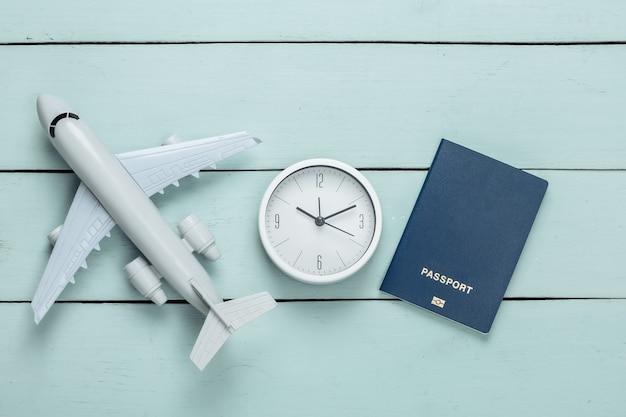 Il est temps de voyager. figurine d'avion et horloge, passeport sur une surface en bois bleue. vue de dessus. mise à plat