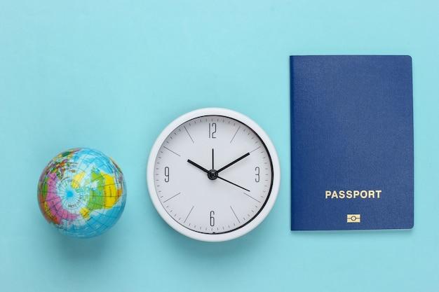 Il est temps de voyager. passeport et horloge, globe sur surface bleue. vue de dessus