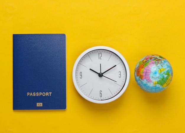 Il est temps de voyager. passeport et horloge, globe sur surface jaune. vue de dessus