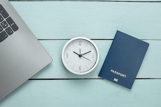 Il est temps de voyager. passeport et horloge, ordinateur portable sur une surface en bois bleue. vue de dessus. mise à plat