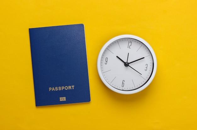 Il est temps de voyager. passeport et horloge sur surface jaune. vue de dessus