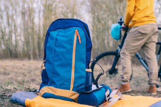 Il est temps de voyager. powerbank charge un smartphone dans la nature avec des sacs à dos en arrière-plan d'un cycliste avec un vélo.