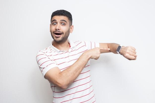 Il est temps d'y aller. portrait d'un jeune homme barbu drôle étonné en t-shirt rayé debout, pointant sur sa montre intelligente, regardant la caméra avec un visage surpris. tourné en studio intérieur, isolé sur fond blanc