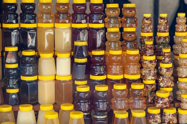 Il existe de nombreux pots de miel biologique et naturel sur le comptoir à vendre. différents miels, différentes couleurs dans des boîtes en plastique sont prêts à être vendus à la foire du miel. noix fourrées au miel.