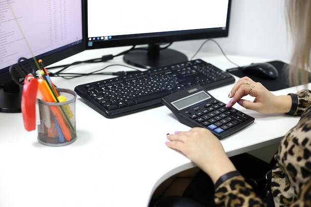 Il fille compte les nombres sur la calculatrice près de l'écran de l'ordinateur