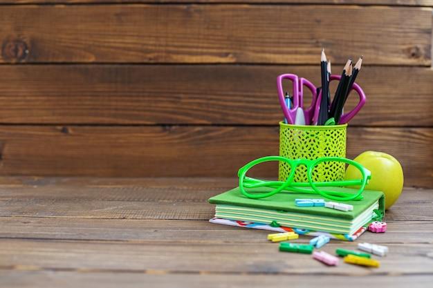 Il livre, crayons et stylos pour l'école. table en bois. le concept