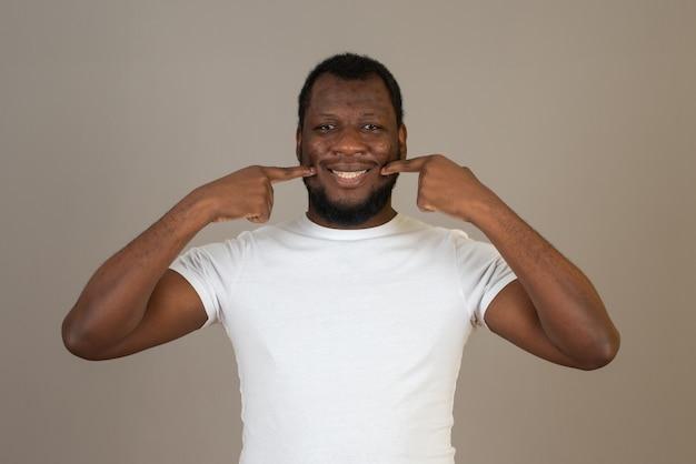 Il montre son visage souriant avec ses doigts, se tient sur un mur beige.