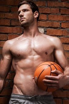 Il ne lâche jamais une balle. low angle view of beau jeune homme musclé tenant un ballon de basket