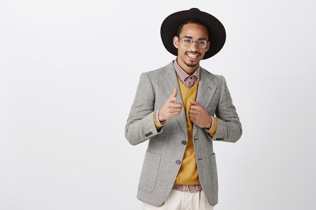 Il peut compter sur vous. portrait d'un homme afro-américain confiant satisfait en chapeau noir et veste élégante, montrant un signe d'armes à feu, renforçant la confiance près du miroir avant de sortir