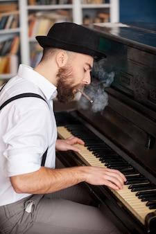 Il a sa propre technique. profil de beaux jeunes hommes barbus jouant du piano et fumant une cigarette