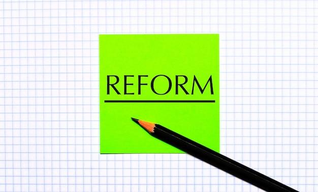 Il y a un autocollant vert avec le texte reform et un crayon noir sur le papier quadrillé
