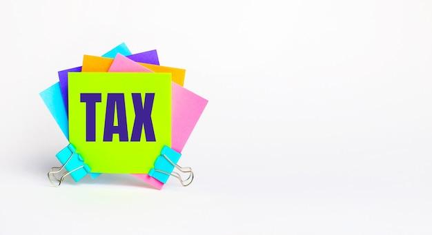 Il y a des autocollants multicolores brillants avec le texte taxe. espace de copie