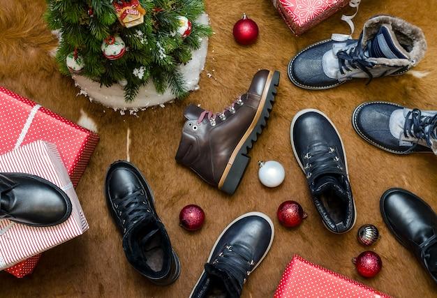 Il y a beaucoup de bottes d'hiver différentes à côté de l'arbre de noël et des boîtes avec des cadeaux. nature morte. vue de dessus.