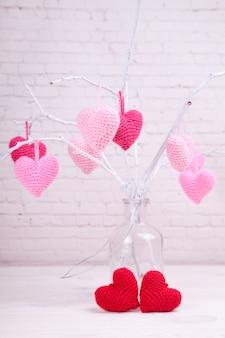 Il y a beaucoup de coeurs tricotés roses sur des branches blanches. bouteille en verre. la saint valentin.