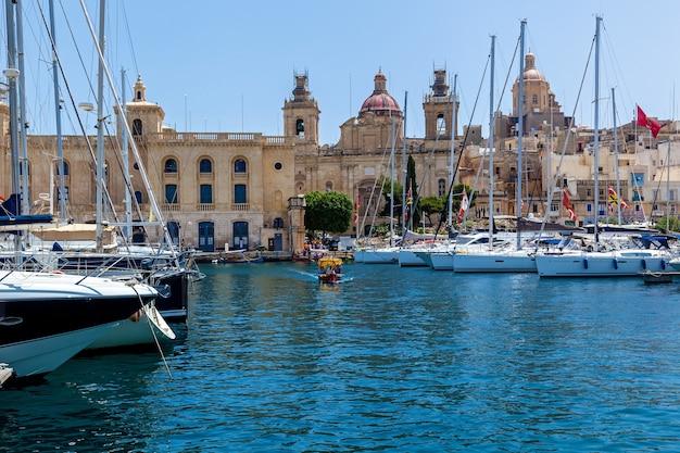 Il y a beaucoup de yachts amarrés dans le port sur le fond de la ville maltaise avec de vieux bâtiments et des palmiers par une journée ensoleillée d'été.