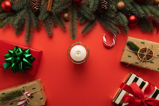 Il y a une bougie sur la table de noël et des boîtes avec des cadeaux