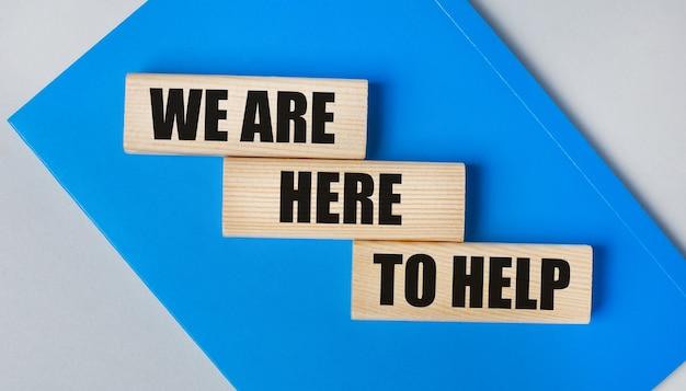 Il y a un cahier bleu sur fond gris clair. au-dessus se trouvent trois blocs de bois avec les mots nous sommes ici pour aider.