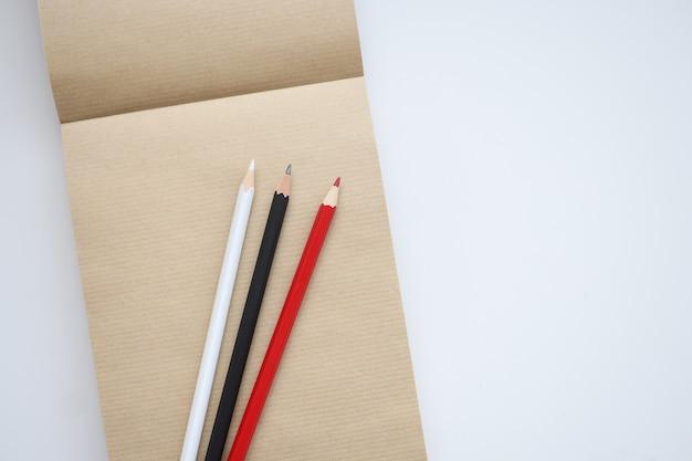 Il y a des crayons blancs et noirs rouges sur le concept de processus créatifs d'apprentissage de bloc-notes