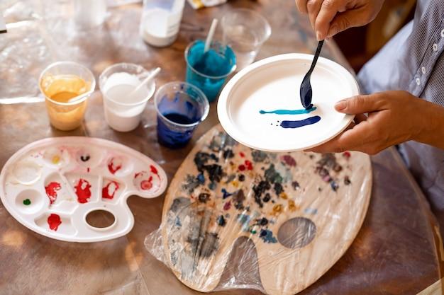 Il y a des peintures dans des tasses sur la table devant l'artiste. elle les applique sur la surface pour voir la combinaison des nuances résultantes. passe-temps . peinture intérieure. processus de création de peintures modernes.