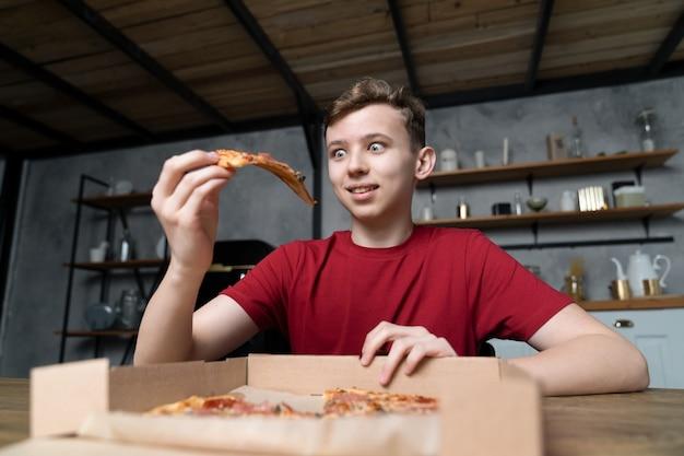 Il y a une pizza sur une table en bois dans une boîte en carton et un jeune homme aux yeux grands ouverts avec plaisir regarde un morceau dans sa main
