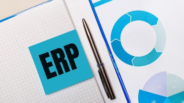 Il y a un stylo entre le pense-bête bleu avec le texte erp et le graphique bleu.