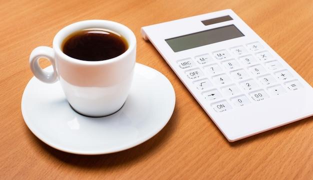 Il y a une tasse blanche avec du café et une calculatrice blanche sur une table en bois. concept d'entreprise