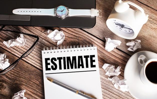 Il y a une tasse de café sur une table en bois, une horloge, des verres et un cahier avec le mot estimation. concept d'entreprise