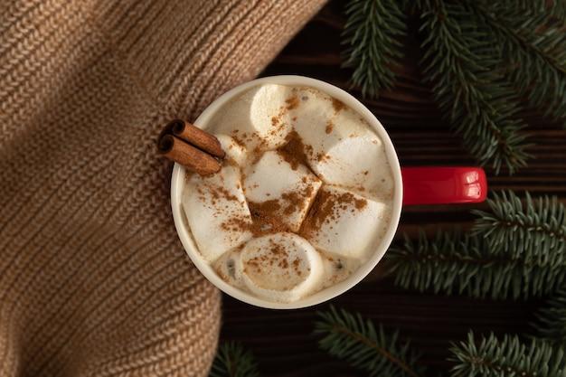 Il y a une tasse de chocolat chaud avec des guimauves sur la table avec un décor de noël