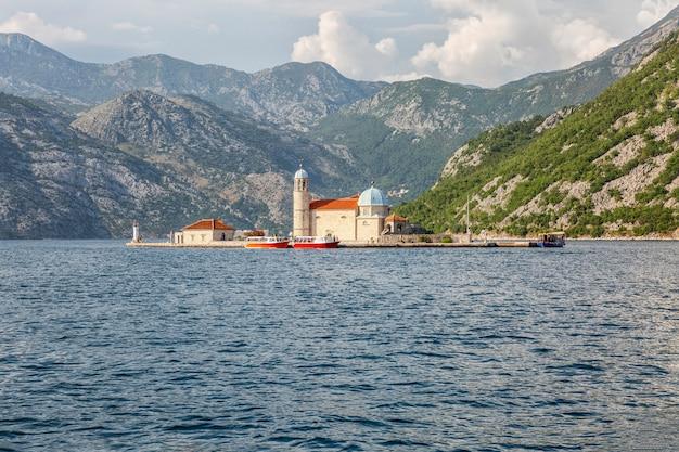 Île avec une église dans la mer sur fond de montagnes à kotor. beau paysage.