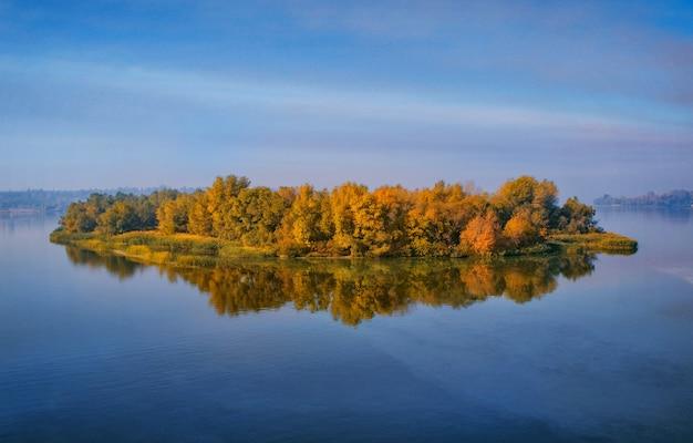 Île avec forêt de feuillus jaunes sur une large rivière