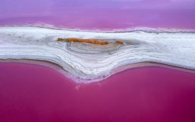 L'île sur le lac rose est recouverte de sel. l'eau rose lave un morceau de rivage sablonneux des deux côtés.