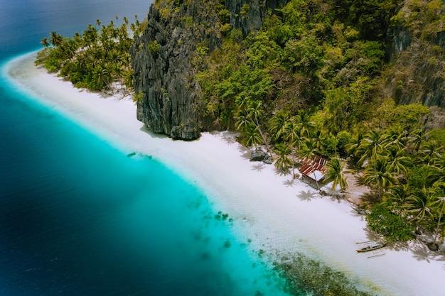 L'île de pinagbuyutan, el nido, palawan, philippines. photo aérienne de drone d'une cabane tropicale entourée de rochers, d'une plage de sable blanc, de cocotiers et d'eau de mer bleu turquoise.