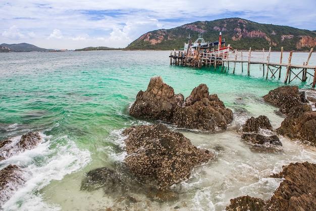Île tropicale avec plage rocheuse et pont en bois