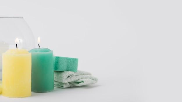 Illuminé des bougies jaunes et vertes avec une éponge et une serviette isolé sur fond blanc