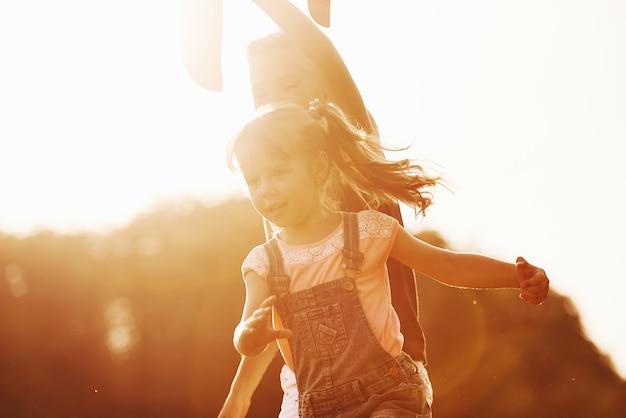 Illuminé par une belle lumière du soleil. fille et garçon s'amusant à l'extérieur dans les mains.