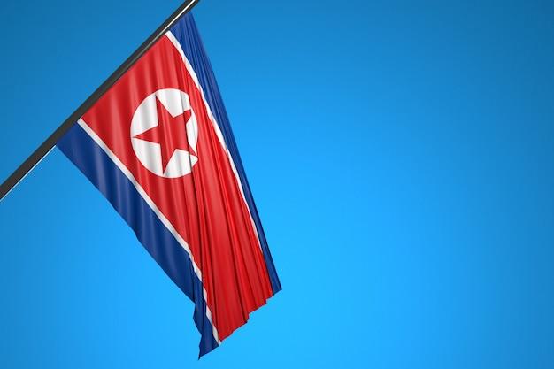 Illustration du drapeau national de la corée du nord sur un mât en métal flottant contre le ciel bleu