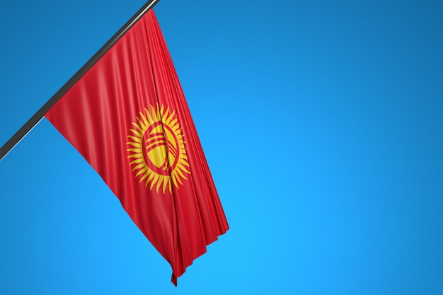 Illustration du drapeau national du kirghizistan sur un mât métallique flottant contre le ciel bleu