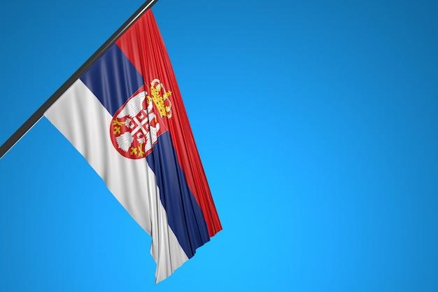 Illustration du drapeau national de la serbie sur un mât en métal flottant contre le ciel bleu