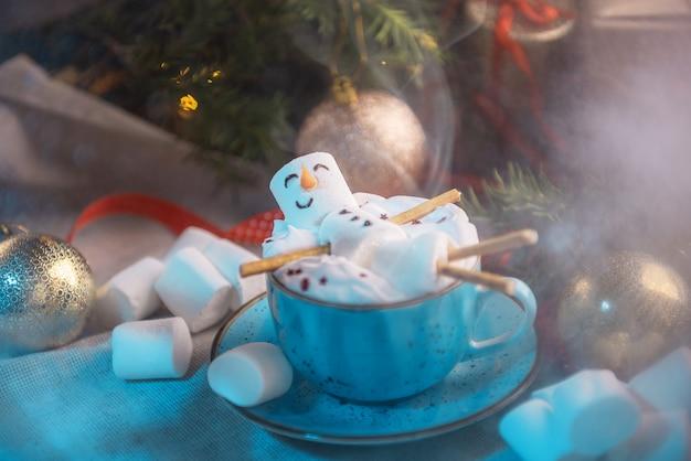 Illustration d'hiver avec une tasse de chocolat chaud dans laquelle se trouve un homme guimauve souriant, tout cela dans les décorations de noël