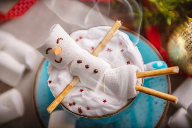 Illustration d'hiver avec une tasse de chocolat chaud dans lequel se trouve un homme guimauve souriant