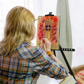 L'illustratrice d'artiste féminin crée une image sur un chevalet