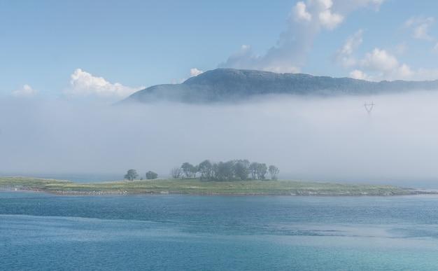 Îlot vert dans une baie bleue dans un brouillard et des montagnes, lofoten, norvège