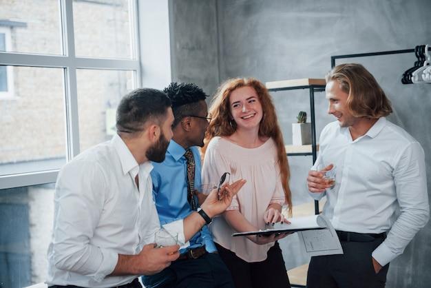 Ils aiment la nouvelle approche. les beaux hommes d'affaires aiment leur travail et partagent leurs idées les uns avec les autres