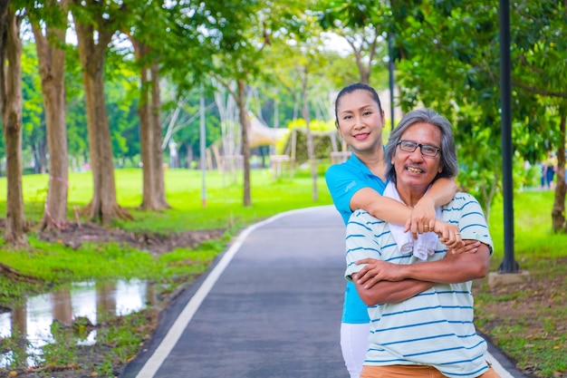 Ils forment un couple asiatique heureux. ils font un gros câlin ensemble après un jogging dans un parc.